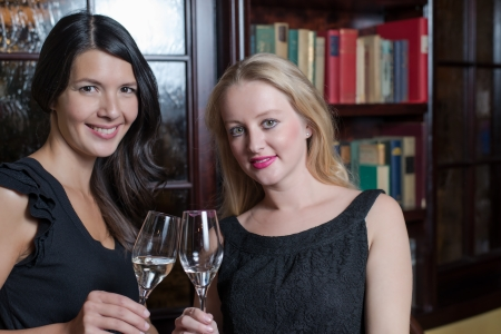 'evening wear': Two elegant sophisticated young women in stylish black evening wear celebrating together drinking flutes of champagne in a hotel library or luxury house interior