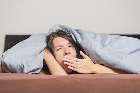 Müde junge Frau Gähnen unter einer Bettdecke und hielt ihre Hand vor den Mund, als sie einen faulen Tag verbringt zu Hause entspannen