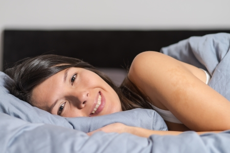 unwinding: Smiling attractive young woman enjoying a lazy day lying on her stomach cuddling on a warm duvet and looking at the camera with a happy smile