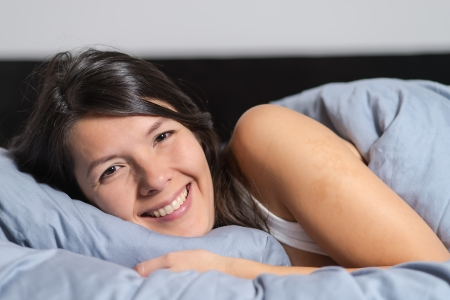 Smiling attractive young woman enjoying a lazy day lying on her stomach cuddling on a warm duvet and looking at the camera with a happy smile