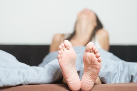 Nahaufnahme des netten gefältelt Sohlen der weiblichen Füße Zugehörigkeit zu einer lächelnden verspieltes Frau Entspannung in ihrem Bett mit dem Fokus auf die Füße