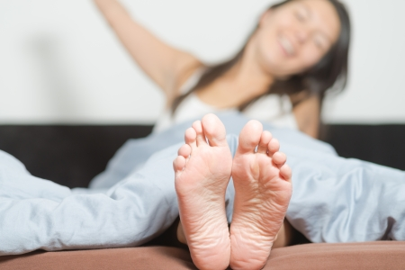 feet soles: Close up of the cute crinkled soles of female feet belonging to a smiling playful woman relaxing in her bed with focus to the feet Stock Photo