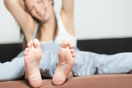 Close up of the cute crinkled soles of female feet belonging to a smiling playful woman relaxing in her bed with focus to the feet photo