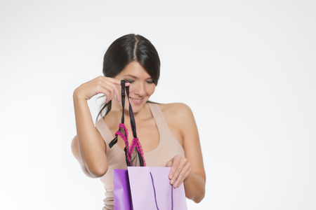 tantalising: Beautiful young woman giving a sneak peek at new lacy lingerie lifting it out of the shopping bag with her finger while giving the camera a teasing smile