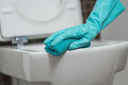 Hand van een persoon het schoonmaken van de wc-bril in rubberen handschoenen met een spons het desinfecteren van de onderkant voor ziektekiemen en bacteriën tijdens het uitvoeren van huishoudelijke taken