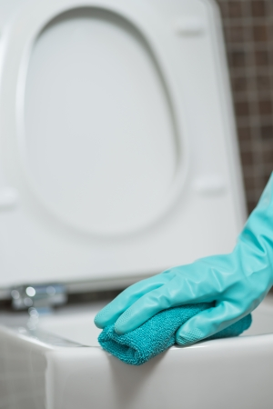 disinfecting: Hand of a person cleaning the toilet seat in rubber gloves with a sponge disinfecting the underside for germs and bacteria while performing household chores