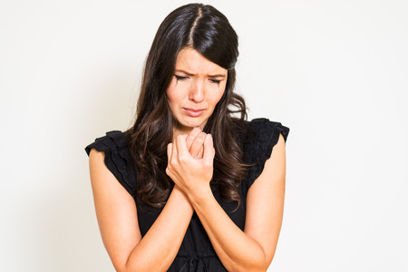 anguish: Attractive young tearful distressed woman with her eyes closed, wringing her hands with a ring in it in anguish against a white background