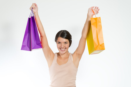 aloft: Brunette happy young woman with raised arms holding shopping paper bags, on gray background