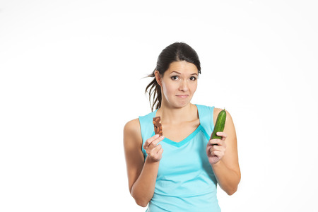 nutritive: Fit young brunette woman undecided before choosing between a nutritious fresh vegetable and a delicious sweet chocolate bar