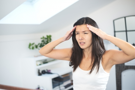 throbbing: Attractive young woman with a migraine headache standing holding her fingers to her temples with her eyes half closed in pain