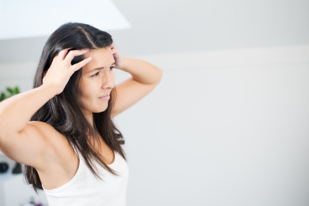 neuralgia: Attractive young woman with a migraine headache standing holding her fingers to her temples with her eyes half closed in pain
