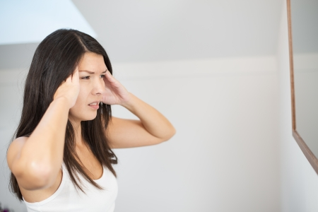 Attractive young woman with a migraine headache standing holding her fingers to her temples with her eyes half closed in pain photo