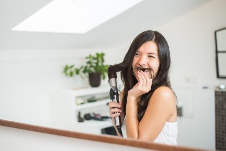 tresses: Playful young woman styling her hair making a pretense moustache with one of her long tresses as she grins at herself in the bathroom mirror Stock Photo