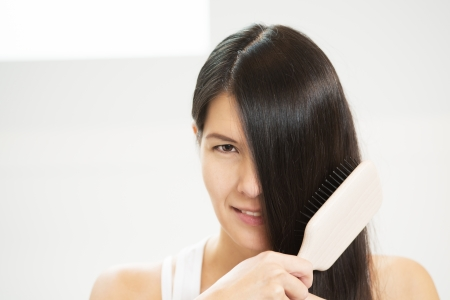 concealed: Attractive woman brushing her hair with one eye concealed by her long brunette locks looking at the camera with a sensual seductive look
