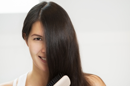 tantalising: Attractive woman brushing her hair with one eye concealed by her long brunette locks looking at the camera with a sensual seductive look