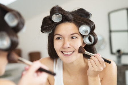 Attractive smiling woman with her long brunette hair done up in large curlers applying makeup in a mirror leaning forwards to see better as she applies blusher with a large soft cosmetics brush