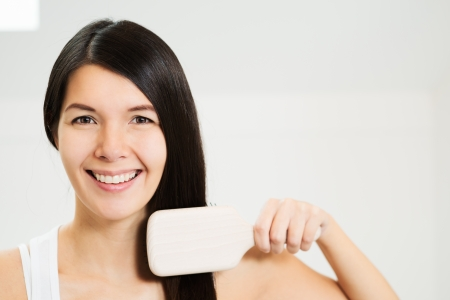 tantalising: Attractive woman brushing her hair looking at the camera with a friendly charming smile