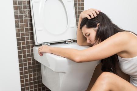 Junge Frau Erbrechen in die WC-Schüssel in den frühen Stadien der Schwangerschaft oder nach einer durchzechten Nacht und Trinken Standard-Bild