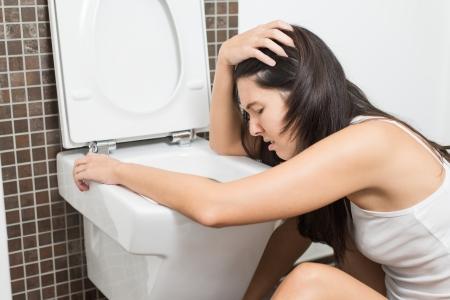 vomito: Mujer joven vomitando en la taza del inodoro en las primeras etapas del embarazo o despu�s de una noche de fiesta y beber Foto de archivo