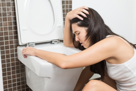 vomiting: Young woman vomiting into the toilet bowl in the early stages of pregnancy or after a night of partying and drinking