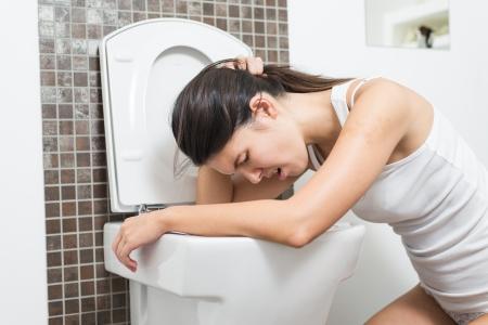 the vomiting: Mujer joven vomitando en la taza del inodoro en las primeras etapas del embarazo o despu�s de una noche de fiesta y beber Foto de archivo