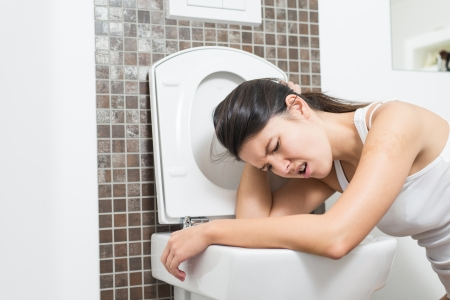 illnesses: Young woman vomiting into the toilet bowl in the early stages of pregnancy or after a night of partying and drinking
