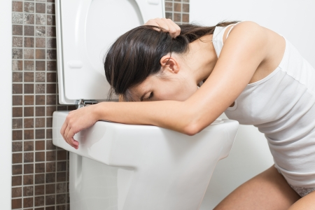 Young woman vomiting into the toilet bowl in the early stages of pregnancy or after a night of partying and drinking photo