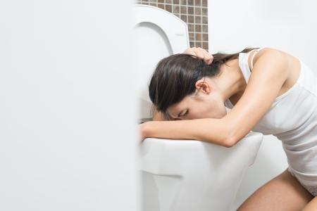 vomito: Mujer joven vomitando en la taza del inodoro en las primeras etapas del embarazo o después de una noche de fiesta y beber Foto de archivo