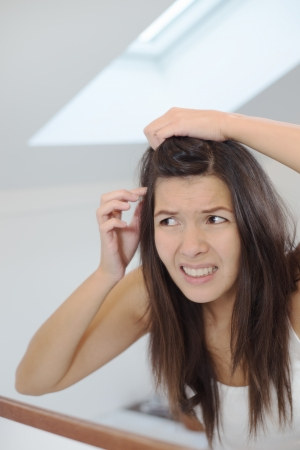 scalp: Horrified young woman looking in the bathroom mirror staring open mouthed at the first grey hair on her scalp, a first sign of ageing, or noticing that she is suffering from dandruff