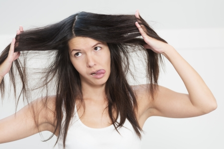 tresses: Attractive young woman unhappy with the condition her long hair standing grimacing at the camera with her hands entwined in her tresses holding the hair out on either side of her face