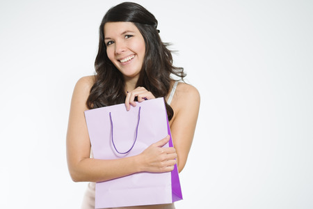 possessive: Elated young woman clutching her purchases in a pretty purple shopping bag close to her chest in a possessive manner as she smiles happily showing her satisfaction, isolated on white