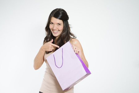 conspiratorial: Happy shopper pointing to her shopping bag with a playful conspiratorial look as she smiles in contentment at the purchase of a surprise gift, isolated with copyspace