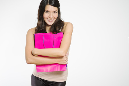 Elated young woman clutching her purchases in a pretty purple shopping bag close to her chest in a possessive manner as she smiles happily showing her satisfaction, isolated on white