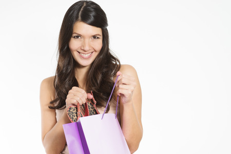 sneak: Smiling attractive young woman happy with her purchase giving the viewer a sneak peek as she lifts it out of a purple shopping bag with a smile of satisfaction and glee, isolated on white