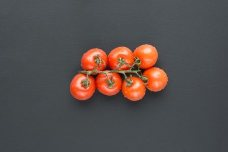 lycopene: Bunch of delicious ripe red fresh cherry tomatoes with water droplets still on the vine, overhead view on a black background