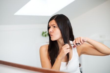shorten: Attractive young woman with long brunette hair preparing to cut it with a pair of scissors in the bathroom grimacing in apprehension as she has misgivings about her decision Stock Photo