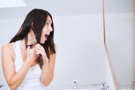 shorten: Atractiva mujer joven con pelo largo Morena preparando para cortar con unas tijeras en el cuarto de ba�o que hace muecas en la aprehensi�n, ya que tiene dudas sobre su decisi�n