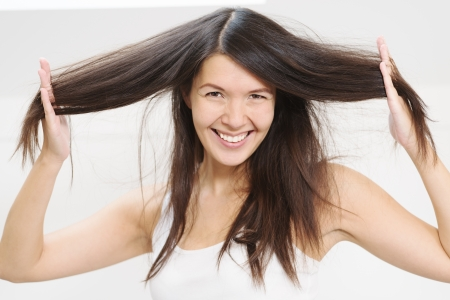 tresses: Joyful beautiful young woman playing with her long brunette hair running her fingers through the tresses as she lifts it away from her head while smiling happily at the camera