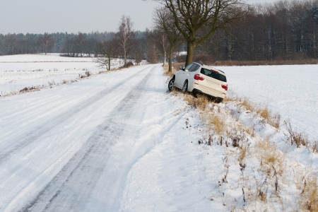 road conditions: White SUV crashed in a country road kerbside due to slippery road covered in snow with skid marks