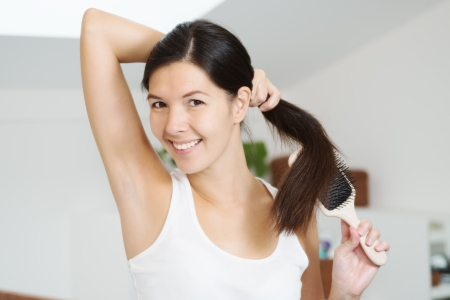 rejuvenated: Smiling attractive woman brushing her long brunette hair in the bathroom in the morning holding it in one hand in a ponytail as she runs the brush through it