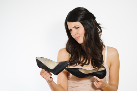 heeled: Beautiful woman deciding between two elegant classic high heeled shoes grimacing as she struggles to reach a decision, isolated on white Stock Photo