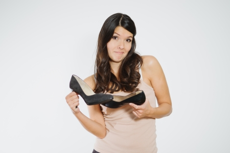deciding: Beautiful woman deciding between two elegant classic high heeled shoes grimacing as she struggles to reach a decision, isolated on white Stock Photo