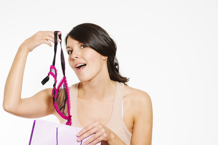 tantalising: Provocative woman with lacy lingerie giving a tantalising peek of a new purchase holding up a sexy lacy bra on her fingertip