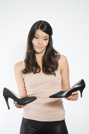court shoes: Smiling attractive woman with long brunette hair showing off a pair of fashionable high heeled classic black court shoes holding one out towards the viewer to show her pleasure with her purchase