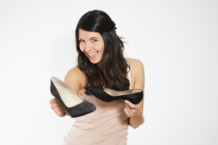 show off: Smiling attractive woman with long brunette hair showing off a pair of fashionable high heeled classic black court shoes holding one out towards the viewer to show her pleasure with her purchase