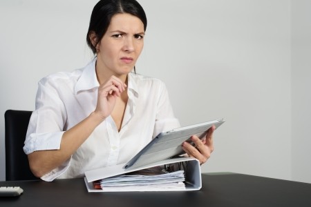 Puzzled woman thinking hard and grimacing as she tries to find an answer to a problem posed on her handheld tablet computer Stock Photo