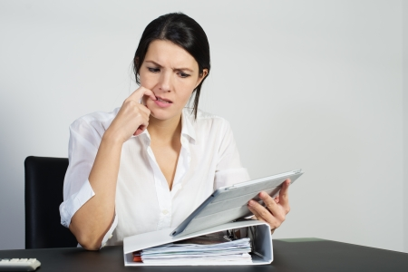 의아해 여자 그녀는 문제에 대한 답을 찾기 위해 시도로 열심히 생각하고 찡그린 그녀의 휴대용 태블릿 컴퓨터에있었습니다