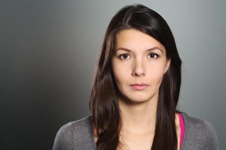 introspective: Studio head and shoulders portrait on grey of a beautiful serious young woman looking directly at the camera Stock Photo