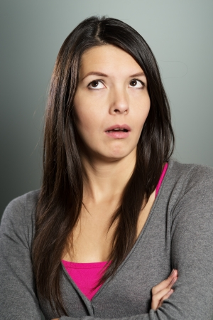 sceptical: Attractive woman with a sceptical bemused expression standing with folded arms pulling a wry face as she looks upwards into the air