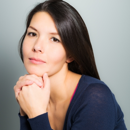 inscrutable: Thoughtful attractive woman with a serene face and enigmatic smile standing with her hand to her chin looking pensively at the camera